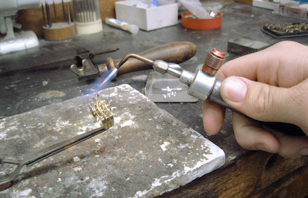 Master jeweler repairing ring on jewelers bench